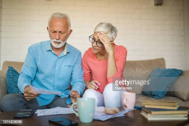 senior couple brainstorming the solution to a financial problem - retirement stock pictures, royalty-free photos & images