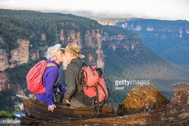 senior couple bushwalkers kissing with spectacular landscape views - blue mountains national park stock pictures, royalty-free photos & images