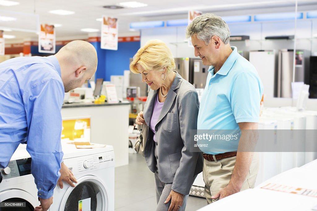 Senior couple buying a washing machine : Stock Photo