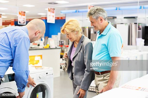 senior couple buying a washing machine - appliance stock pictures, royalty-free photos & images