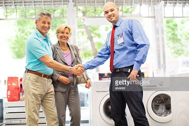 senior couple buying a washing machine - electronics store stock photos and pictures