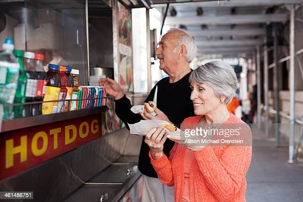 Senior couple buying food from street vendor