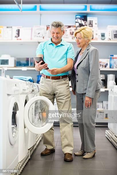 Senior couple buying home appliance
