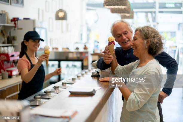 Senior couple buying ice cream at the ice cream parlor and friendly saleswoman serving ice creams