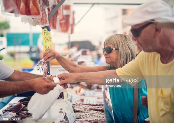 Senior couple buying traditional Spanish meat at the farmer's market