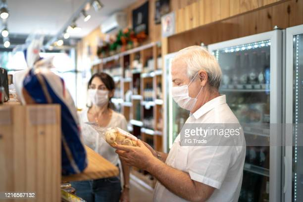 senior couple buying with face mask at store - illness prevention stock pictures, royalty-free photos & images