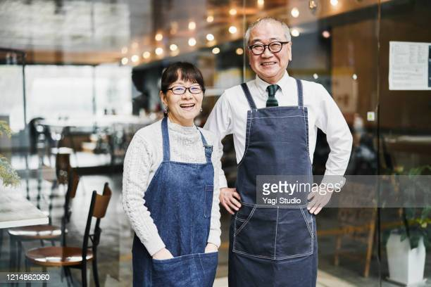 senior couple cafe owners working happily in cafe together - disruptaging stock pictures, royalty-free photos & images