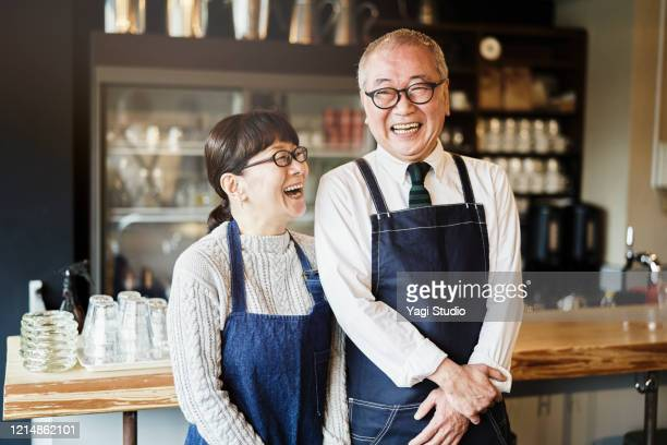 senior couple cafe owners working in cafe together - small business stock pictures, royalty-free photos & images