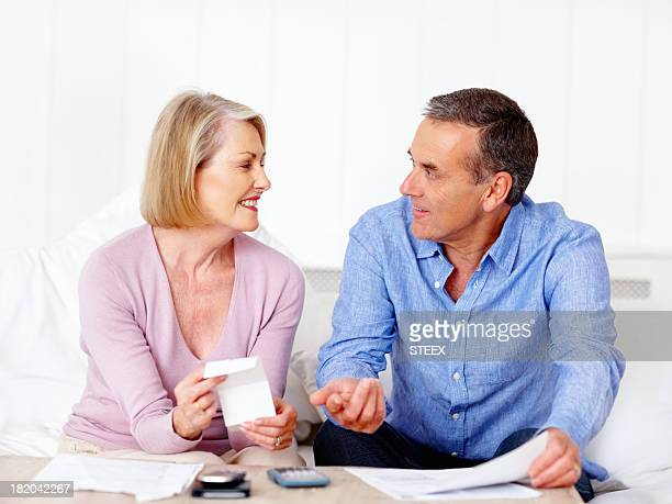 Senior couple calculating expenses with the help of calculator