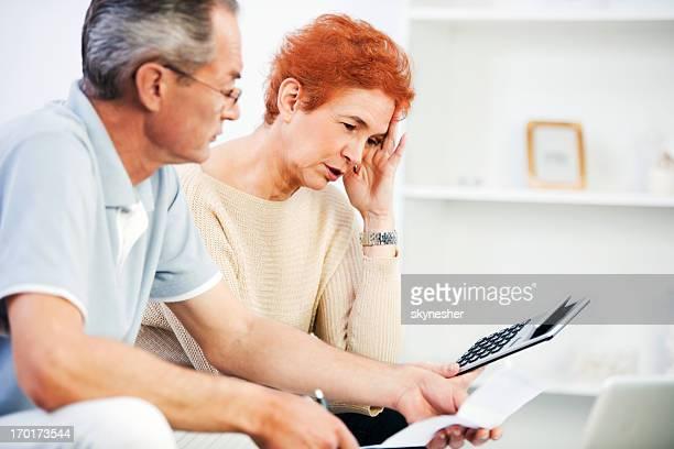 Altes Paar Berechnung Ihrer monatlichen Finanzen zu Hause fühlen.