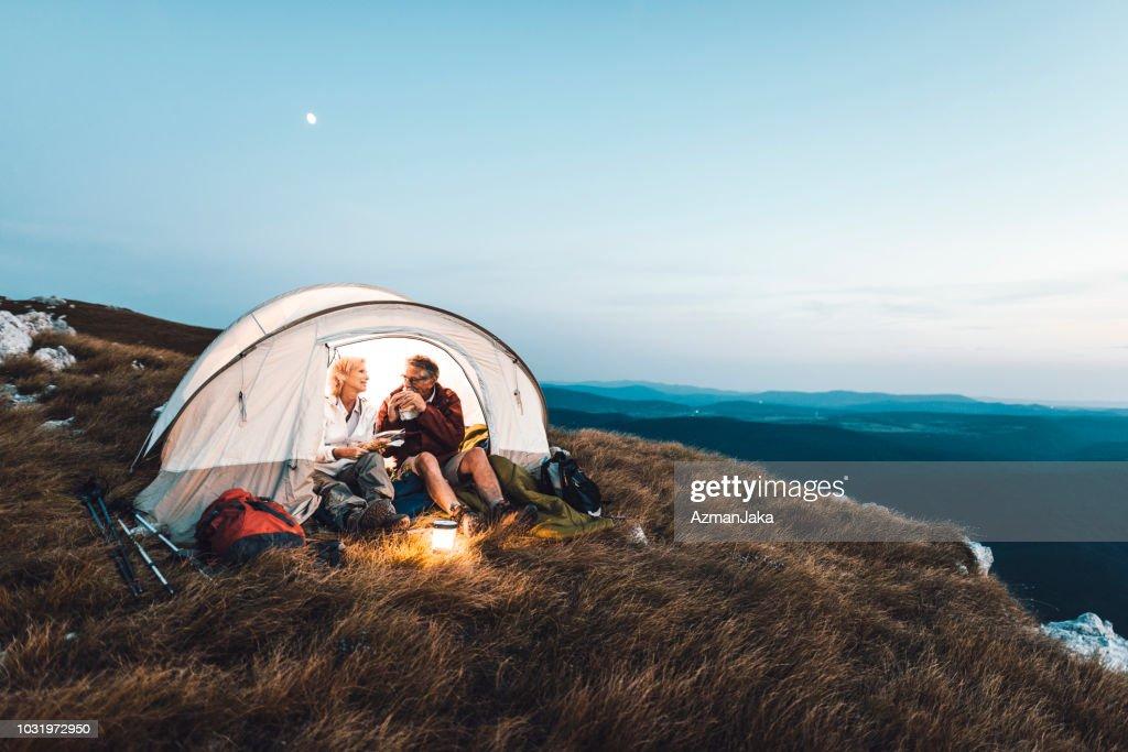 Coppia senior in campeggio in montagna e mangiare uno spuntino : Foto stock