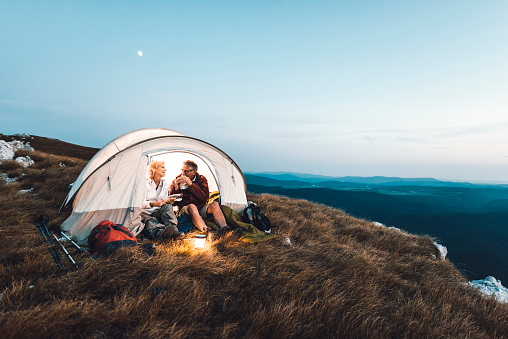 Senior couple camping in the mountains and eating a snack 1031972950