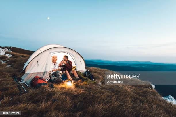 senior couple camping in the mountains and eating a snack - camping stock photos and pictures