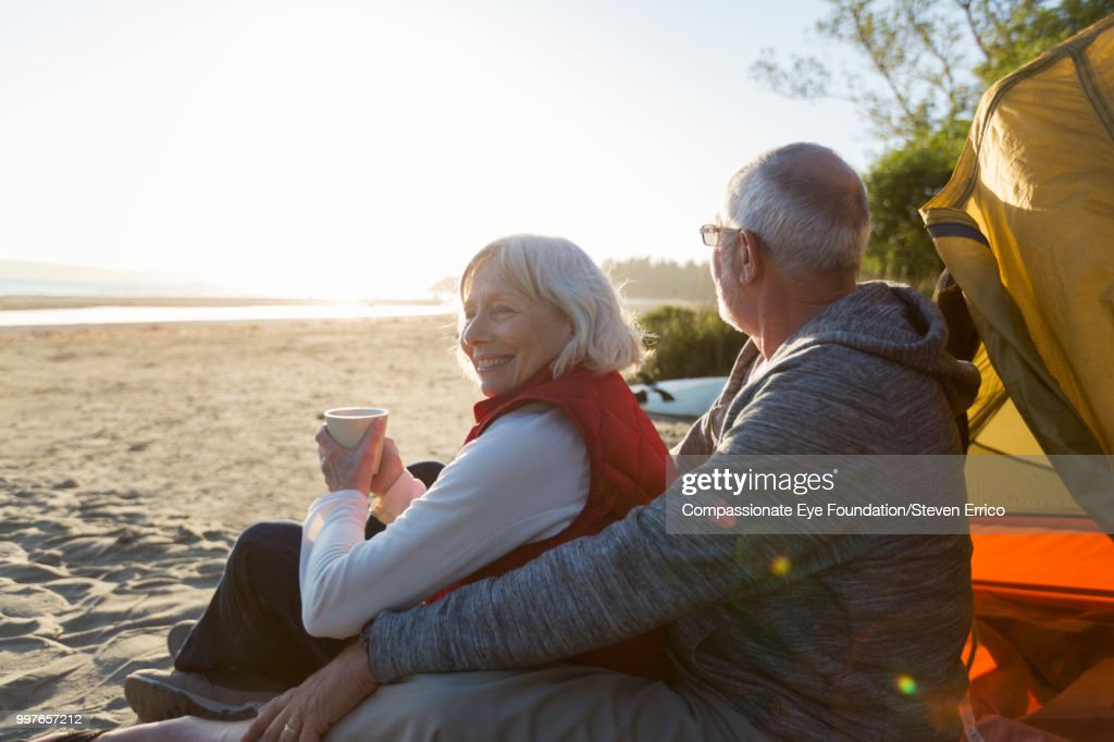 Senior couple camping on beach looking at ocean view : Stock Photo