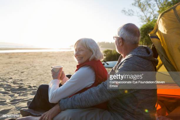 senior couple camping on beach looking at ocean view - outdoor pursuit stock pictures, royalty-free photos & images