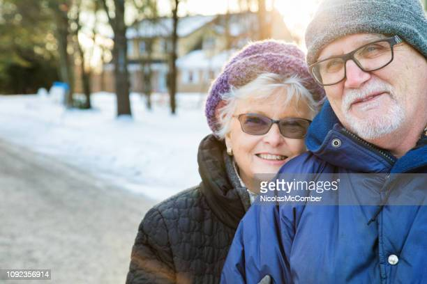 senior couple candid portrait during a winter walk in suburbs - january stock pictures, royalty-free photos & images