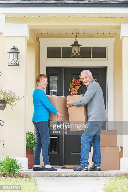 senior couple carrying boxes to front door of house - layoff stock photos and pictures