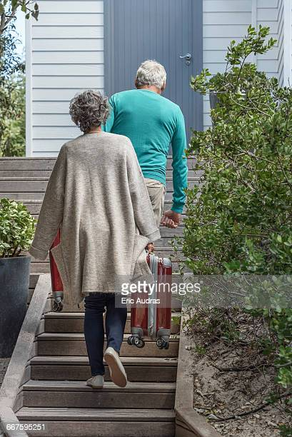 Senior couple carrying suitcase on staircase