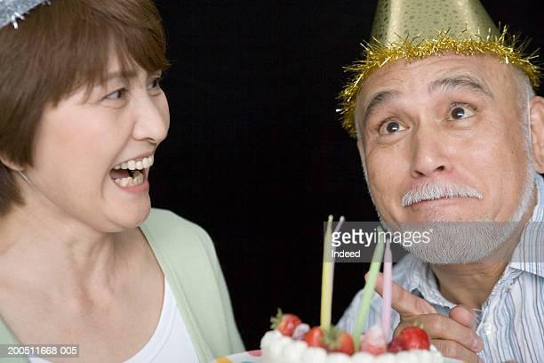 Senior couple celebrating birthday, man pulling funny face, close-up