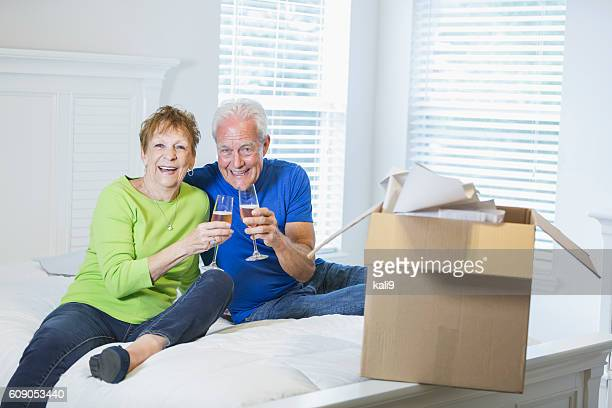 senior couple celebrating move with champagne - layoff stock photos and pictures