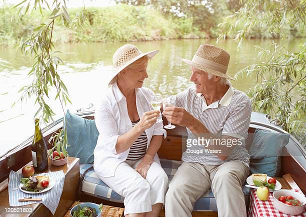 Senior couple celebrating on boat.