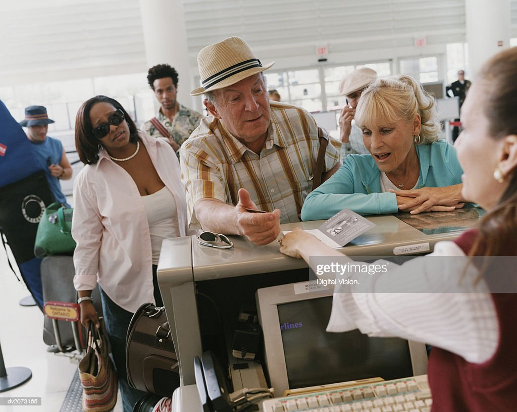 Senior Couple Check In at an Airport : Stock Photo