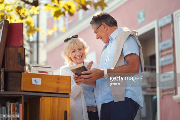 senior couple checking books at flea market - flea market stock pictures, royalty-free photos & images