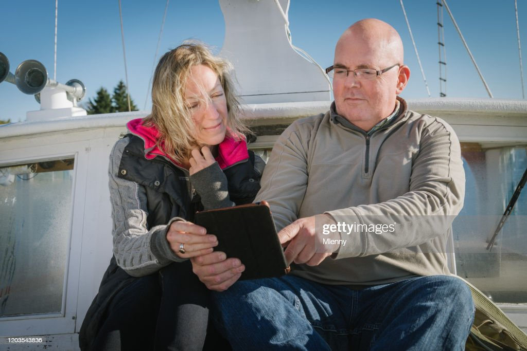 Senior Couple Checking Digital Tablet Computer On Their Sailboat : Stock Photo