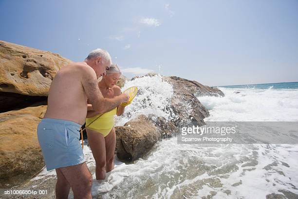 Senior couple checking fishing net in ocean