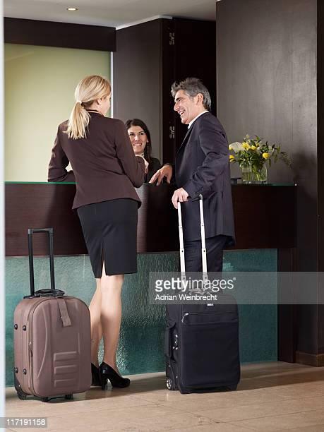 年配のカップルのチェックには、ホテルのフロントデスク