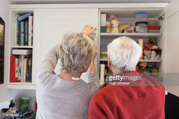 senior couple checking kitchen cupboards - domestic kitchen stock pictures, royalty-free photos & images