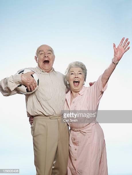 Senior couple cheering as man is holding football