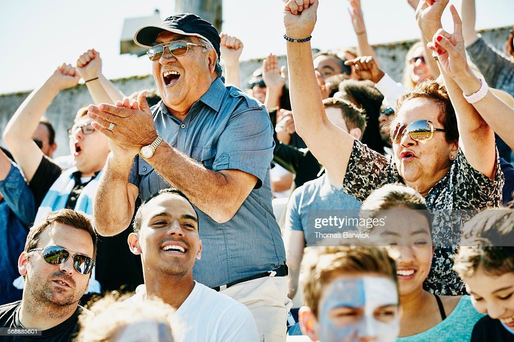 Senior couple cheering in stadium during match : Stock Photo