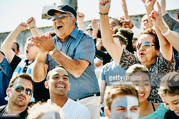 Senior couple cheering in stadium during match