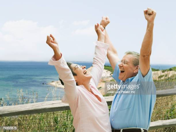 Senior couple cheering outdoors