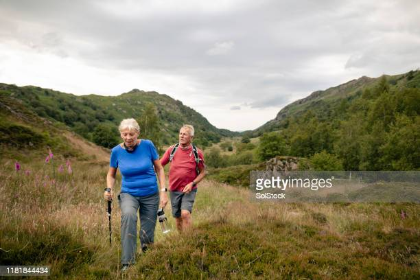 senior couple climbing the hills in the lake district - walking stock pictures, royalty-free photos & images