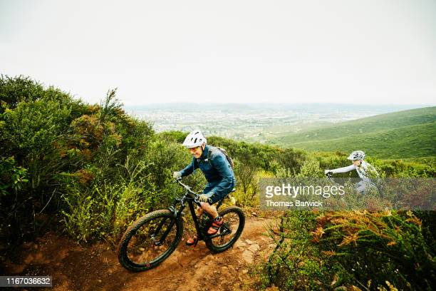 senior couple climbing up trail during early morning mountain bike ride - disruptaging stock pictures, royalty-free photos & images