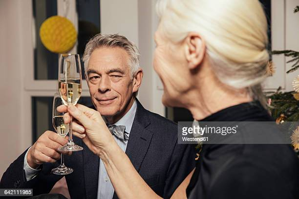 Senior couple clinking glasses with champagne on New Year's Eve