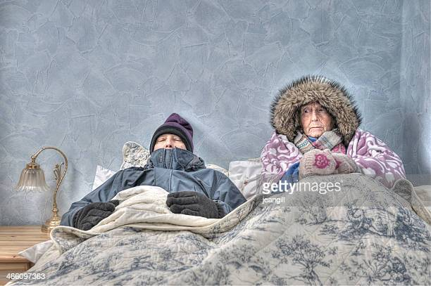 senior couple, cold and miserable in bed - cold temperature stock pictures, royalty-free photos & images