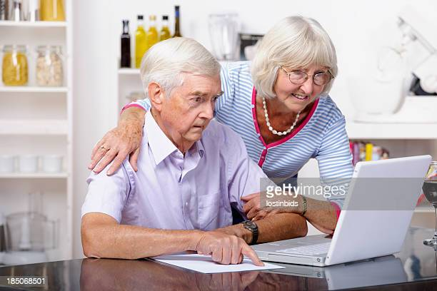Senior Couple Comparing Paper Statement To Internet Record