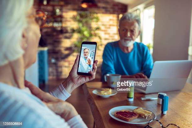 senior couple consulting with their doctor - telemedicine stock pictures, royalty-free photos & images