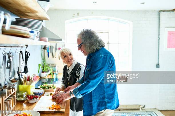 senior couple cooking healthy food together at home - disruptagingcollection stock pictures, royalty-free photos & images