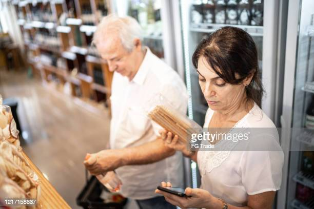 senior couple customer buying using mobile phone at store - baby boomer stock pictures, royalty-free photos & images