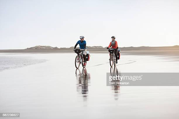 Senior couple cycling on deserted beach