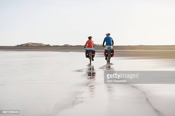senior couple cycling on deserted beach - adventure stock pictures, royalty-free photos & images
