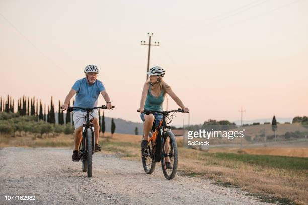 senior couple cycling on holiday - expatriate stock pictures, royalty-free photos & images