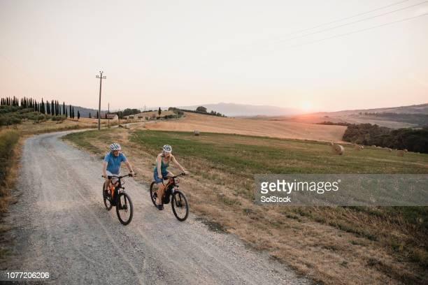 senior couple cycling on holiday - esplorazione foto e immagini stock