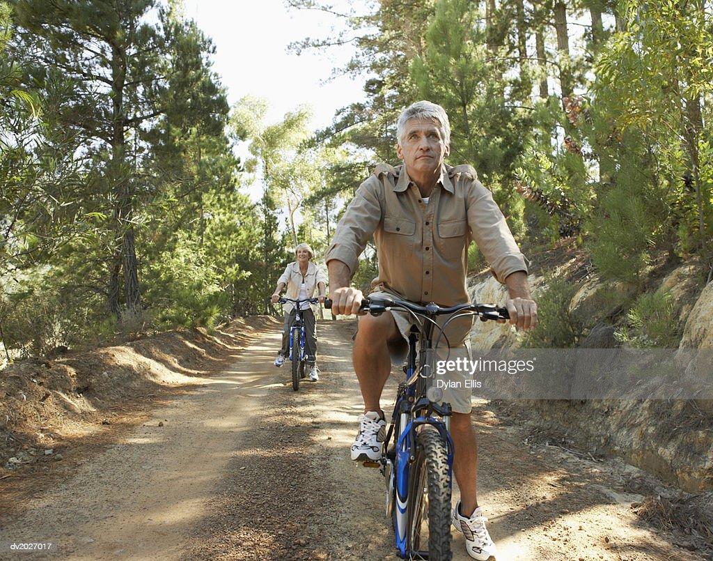 Senior Couple Cycling Through Woodland : Stock Photo