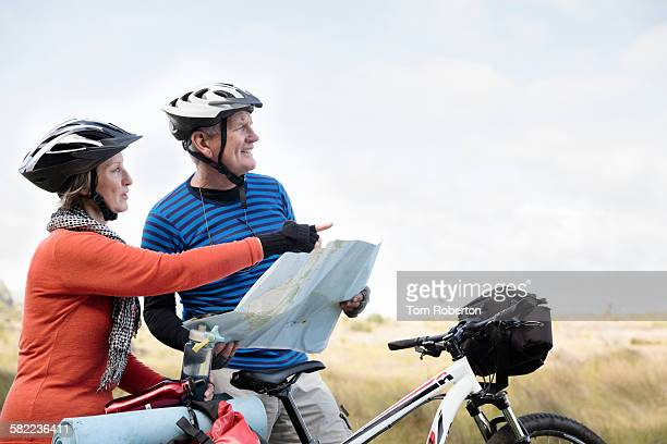 Senior couple cyclists looking at map