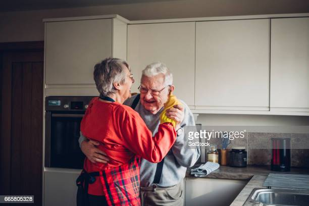 senior couple dance in their kitcchen - common stock pictures, royalty-free photos & images